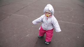 Litet varm-klätt barn omkring 1 år och en månad som lär att gå över gatan Vår långsam rörelse