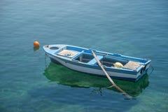 Litet vitt blått fartyg med skovlar som ankras på kusten royaltyfri foto