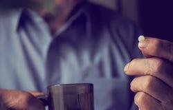 Litet vitt piller i en pensionärs händer Smärtsam gamling Att bry sig för hälsan av åldringen royaltyfri foto