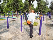 Lithe man working out on public equipment in the park. Lithe man working out on the public equipment in the park of the Temple of Heaven, Beijing Royalty Free Stock Image