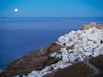 A lithe road leading to Chora of Astypalaia in blue hour and the. Full moon rising from the horizon Royalty Free Stock Photography