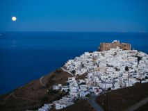 A lithe road leading to Chora of Astypalaia in blue hour and the. Full moon rising from the horizon Royalty Free Stock Photos