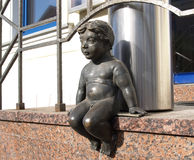 Lithuania, Klaipeda. Sculpture of the naked boy sitting on a por. Ch of the building Royalty Free Stock Photos