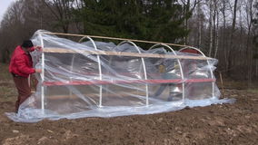 Lithuania, Panevezys district – April 16: workers in farm make new plastic greenhouse, April 16, 2014 stock video footage