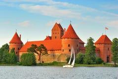 Lithuania. View on Trakai castle across lake. And white yacht under sail stock photos