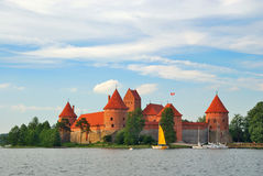 Lithuania. View on Trakai castle across lake. And yacht under yellow sail stock photos