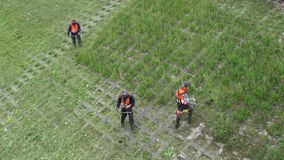Lithuania, Vilnius – May 30: workers with power tool string lawn trimmer mower cutting grass near Neris river, May 30, 2014. Vilnius, Lithuania stock footage