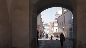 lithuania vilnius Folk som står i port av Dawn In Sunny Spring Day Berömd klosterbroder, historiskt och kulturellt stock video