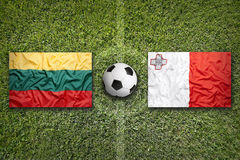 Lithuania vs. Malta flags on soccer field Stock Photo