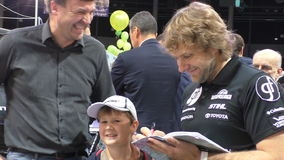 Lithuanian celebrity Dakar rally driver gives autograph to young fan. PANEVEZYS, LITHUANIA - SEPTEMBER 25, 2015: famous Lithuanian celebrity Dakar rally driver