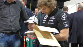Lithuanian celebrity racer signing his book. PANEVEZYS, LITHUANIA - SEPTEMBER 25, 2015: famous Lithuanian celebrity Dakar rally driver and co-author Benediktas