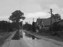 Lithuanian countryside. Road after rain in monochrome Royalty Free Stock Image
