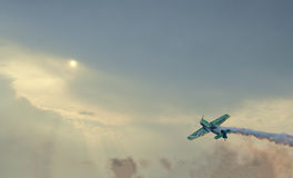 The Lithuanian pilot Jurgis Kairys with his colored airplane training in the blue sky towards shiny sun Stock Photos