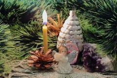 Litjulljus, ängelstatyett med flöjten, julgrangarnering, ametist och att sörja kottar mot bakgrund av gräsplan royaltyfri foto