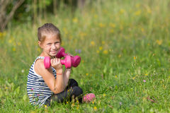 Litl girl with dumbbells sitting on a green meadow. Ten-year-old girl with dumbbells sitting on a green meadow Stock Image