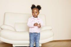 Litle逗人喜爱甜非裔美国人女孩使用满意对玩具在家,生活方式儿童概念 免版税库存照片