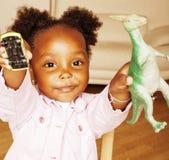 Litle逗人喜爱甜非裔美国人女孩使用满意对玩具在家,生活方式儿童概念 免版税库存图片
