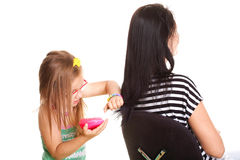 Litle baby girl brushing her mothers hair Royalty Free Stock Photography