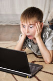 Litle boy with laptop. Boy watching scary movie on a laptop at home Royalty Free Stock Photos