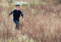 Litle boy runs through the prairie Stock Photo