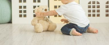 Litle boy sits on the floor stock images