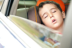 Litle boy sleeps in safe chair. In car with window open Stock Photography