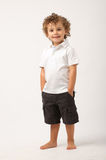 Litle boy standing with his hands on his pockets Royalty Free Stock Photos