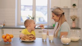 Litle caucasian blonde boy having fun with young mom. Young mother teasing boys pancakes. Happy family having breakfast stock video footage