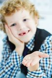Litle caucasian boy holds a dropped milk tooth between his fingers and laughs. Selective focus on the tooth. royalty free stock photos