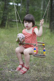 Litle cute girl sitting on swing. Stock Images