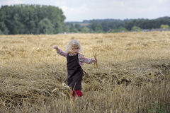 Litle gilr playin in a wheat field Royalty Free Stock Images