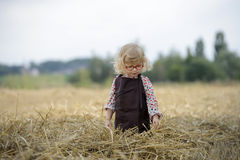 Litle gilr playin in a wheat field Royalty Free Stock Image