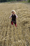 Litle gilr playin in a wheat field Stock Image