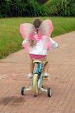 Litle girl biking in the park Stock Photos