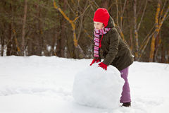 Litle Girl Rolling Big Snowball Royalty Free Stock Photo
