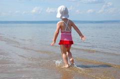 The litle girl runs on water Royalty Free Stock Image