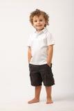 Litle Junge, der mit seinen Händen auf seinen Taschen steht lizenzfreie stockfotos