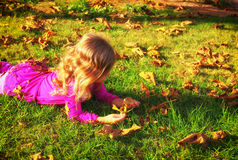 Litle lovely girl playing on the grass in the park and  a sunset  light on her long hair . filtered image Stock Images