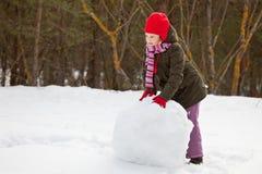 Litle Mädchen, das großen Schneeball rollt Lizenzfreies Stockfoto