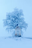 Litle old chapel and od tree with rime and snoow, foggy Christmas day near the road during winter Royalty Free Stock Photos