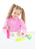 Litli girl sitting at table and writing with ballpoint pen isola Royalty Free Stock Photo