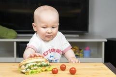 Litlle婴儿白种人男孩设法窃取一根不健康的可口热狗用从桌的蔬菜沙拉 库存图片