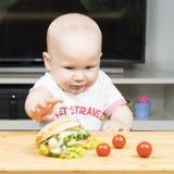 Litlle婴儿白种人男孩设法窃取一根不健康的可口热狗用从桌的蔬菜沙拉 免版税库存图片