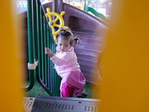 Litlle Asian baby girl enjoys walking up stairs at a children playground royalty free stock photo