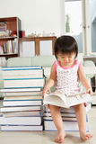 Litlle girl reading lot of books Royalty Free Stock Images