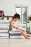 Litlle girl reading lot of books Stock Photo