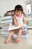 Litlle girl reading lot of books Stock Photography