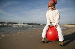 Litlle girl on a red space hopper Royalty Free Stock Photography