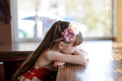 Litlle girl sitting at a table in restaurant Stock Photos
