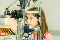 Litlle girl taking the eye exam test Royalty Free Stock Photography